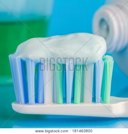 Toothpaste on the toothbrush green dental rinse toothpaste tube on blue background focus on foreground macro image