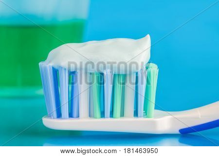 Toothpaste on the toothbrush green dental rinse on blue background focus on foreground macro image