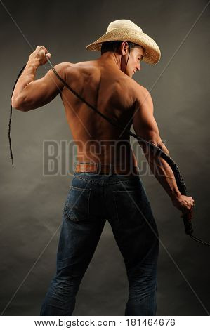 The handsome cowboy is holding his lasso.