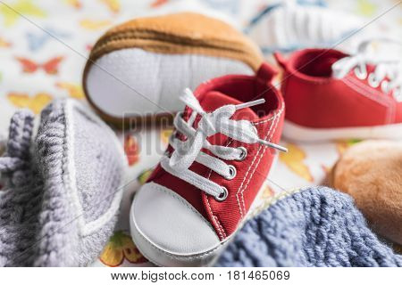 Children's red sneakers with white laces, beige fur boots, gray and blue booties on a light background