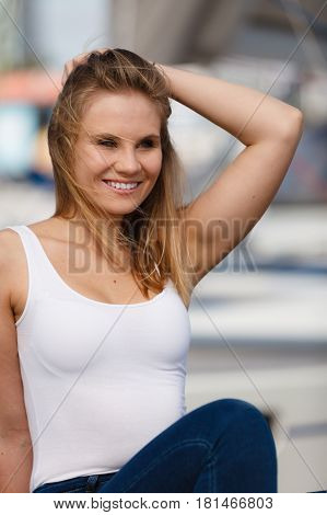 Gorgeous lovely blondie girl portrait. Attractive happy cute girl in white t-shirt on marina place.