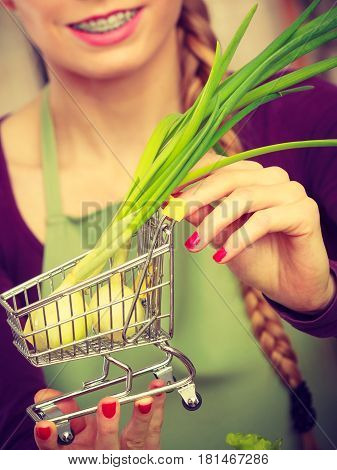 Buying healthy dieting food concept. Woman in kitchen having many green vegetables holding small shopping cart trolley with chive inside.