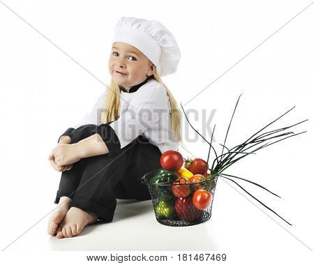 An adorable preschool chef happily sitting by a basket of fresh vegetables.  On a white background.