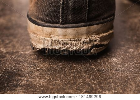 Old black sneakers on a dark marble background. Footwear for outdoor activities. The old sole. Leaky sole. The sole on the shoe has worn off
