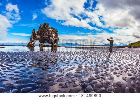 The Basalt rock - Monster Hvitsercur during an ocean outflow. The elderly woman photographs the natural wonder. Concept of extreme northern tourism in Iceland