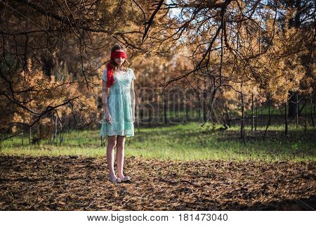 Slavery. Very cute young girl with a blindfold red ribbon. Doll appearance. Woman with brown hair in a turquoise dress on nature. Long hair. Natural light. Model posing on the nature. Kidnapping