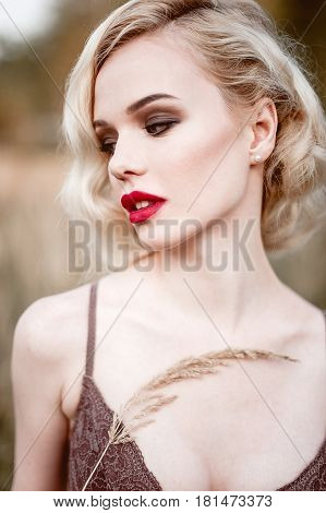 Beautiful And Elegant Smiling Sexy Blonde Woman With Red Lips And Hair Waves Wearing Beige Liingerie