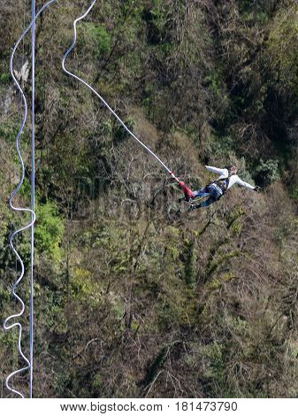 Sochi - April 4 2017: A brave man with a rubber rope jumping from the world's longest pedestrian bridge in the Akhshtyrsky gorge April 4 2017 Sochi Russia