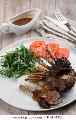 Roasted lamb ribs with rocket salad and tomato on a rustic table