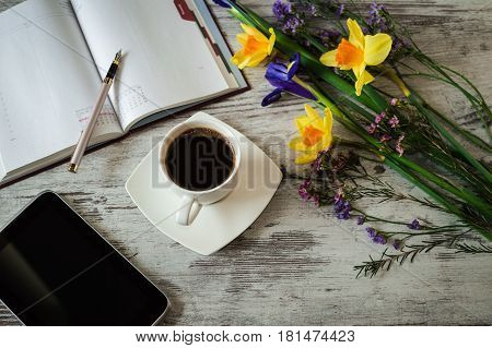 A cup of black coffee, pen, tablet and notes on a white wooden background.Beautiful yellow daffodils, lilac irises and little spring flowers.