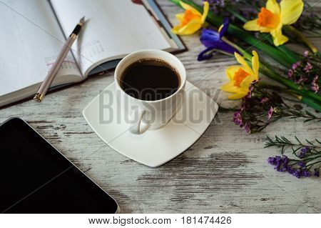 Aromatic work morning with cup of black coffee, tablet and notes. Beautiful yellow daffodils, lilac irises and little spring flowers on a white wooden background.