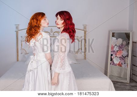 Two beautiful edwardian girls with red hair in a beautiful white wedding victorian and edwardian dresses. Female style. The fragile edwardian girl. Thin waist. Edwardian model
