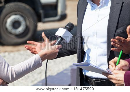 Reporters interviewing businessman, holding microphone and writing notes