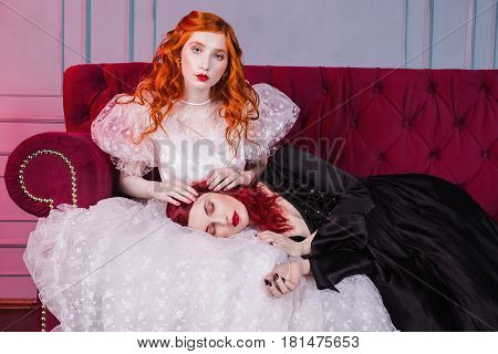 Two charming girls with red hair in retro dress in the bedroom. Femme fatale in a black dress and nice charming girl in white wedding dress. Fairy and Witch. Charming model posing in studio. Historical renaissance dresses.