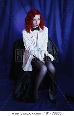 Woman with long red curly hair in white unbuttoned shirt and black bow tie and stockings on blue background. Red-haired girl with pale skin unusual appearance red lips. A prostitute burlesque model