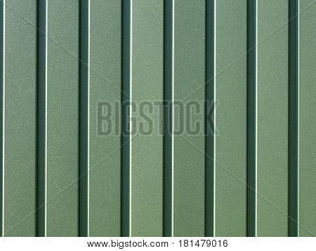 Greenery metallic fence made of corrugated steel sheet with vertical guides. Corrugated green iron sheet background close up.