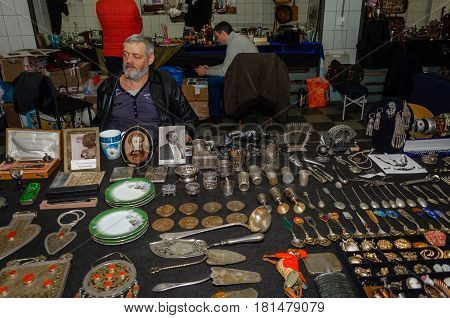 Moscow, Russia - March 19, 2017: Seller of antique cutlery in the flea market in anticipation of buyers