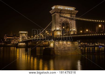 The lights on Chain Bridge in Budapest reflect off the smooth flowing water of the Danube River at winter.