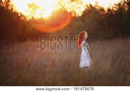 A woman with red curly hair in white sundress on background of dawn. Red-haired girl with pale skin bright unusual appearance and red lips and thin waist in the field on background of rising sun.