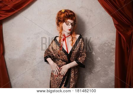 A vintage woman with red hair in leopard print gown with vintage glasses in hand. Red-haired vintage girl with pale skin and blue eyes with a bright unusual appearance with a red ribbon around her neck. French vintage courtesan