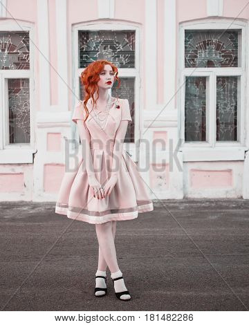 A woman with red curly hair in a peach dress on background vintage window. Red-haired girl with pale skin blue eyes a bright unusual appearance and red lips and a thin waist with beads on her neck