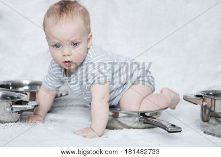 Mother's helper in a set of pots and pans. Infant boy playing with a set of dishes.