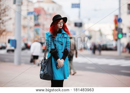 Woman with red curly hair in blue coat and black round glasses on background of big city. Red-haired girl with pale skin and bright appearance with black hat on head and bag on shoulder. Street style in big city. Model in city street