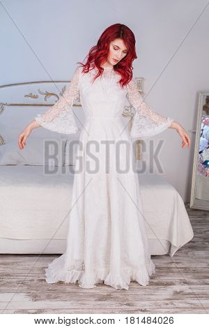 Beautiful princess girl with red hair and natural make-up and pale skin. A woman princess in a white dress renaissance. Model princess posing in studio. The unusual appearance. The bride in the bedroom. Princess in dress