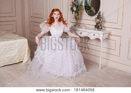 Woman aristocrat with long red curly hair in a white vintage wedding dress with white pearl earrings on her ears. Red-haired aristocrat girl with pale skin blue eyes a bright unusual appearance in the luxurious bedroom. Model aristocrat