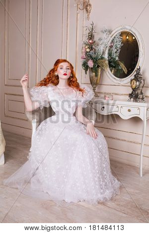 Stylish woman with long red curly hair in a white vintage wedding dress with white pearl earrings on her ears. Red-haired stylish girl with pale skin blue eyes a bright unusual appearance in the luxurious stylish bedroom. Stylish model in white stylish we
