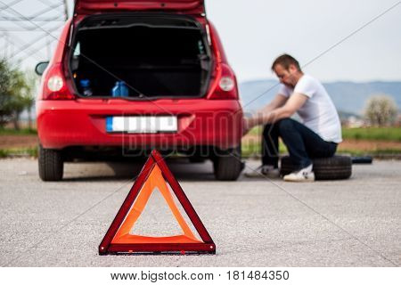 Car remained in trouble on the road the red triangle placed behind the car the driver concerned is trying to refuse to malfunction