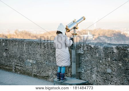 A girl looks through the viewing binoculars on the viewpoint on the hill in the Austrian city of Salzburg - hometown of Mozart.