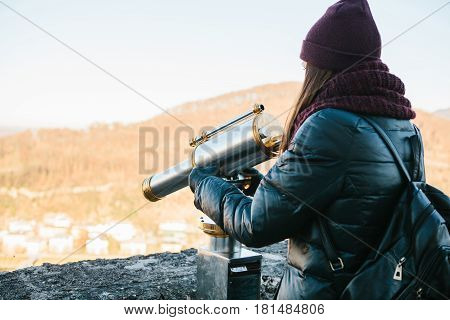 Young girl looks through the viewing binoculars on the lookout on the hill in the Austrian city of Salzburg - hometown of Mozart.