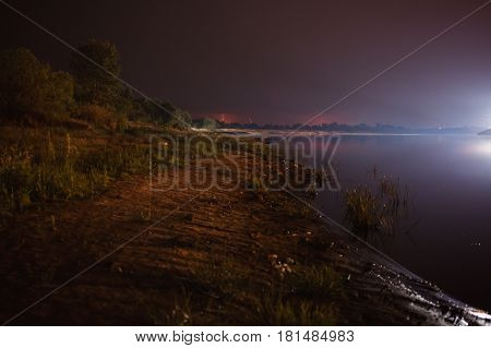 Bolts of lightning over the river. Thunder Sky. The beautiful night scenery. Slow shutter speed. The spectacular sky. Scenic view. The surface of the water