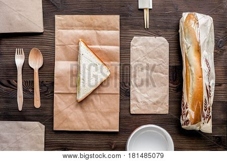 delivery service set with paper bags and sandwich on wooden desk background top view space for text