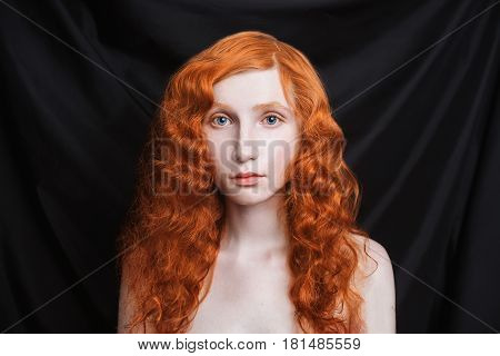 Romantic woman with long curly red flowing hair on a black background. Red-haired romantic girl with pale skin blue eyes bright unusual appearance without makeup. Natural beauty. Romantic girl from the era of renaissance.