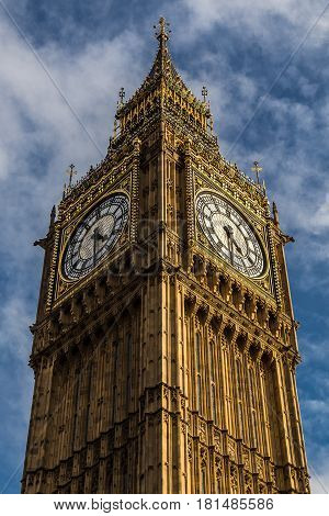 Simplistic view of the tower encasing Big Ben against a blue autumnal sky.