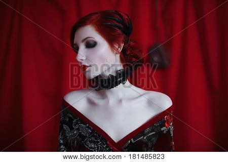 A noir woman with red curly hair in a black dress and retro makeup on a red background. Red-haired noir girl with pale skin blue eyes a bright unusual appearance red lips and a fatal face. Noir woman. Noir model