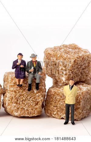 Miniature people: seniors, in front, cubes of brown sugar.