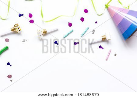 Colored party set with hat and confetti on white table background top view mock up
