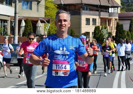 CLUJ-NAPOCA ROMANIA - APRIL 9 2017: Unidentified marathon runners compete at the Wizz Air Cluj-Napoca Marathon. Group of people of all ages run on the streets of the town.