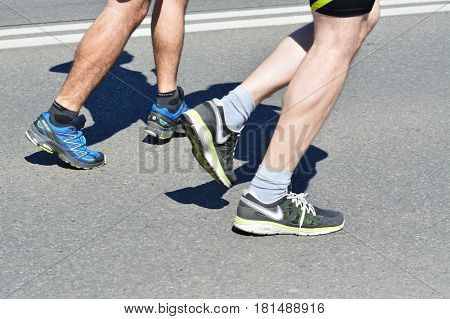 CLUJ-NAPOCA ROMANIA - APRIL 9 2017: Unidentified marathon runners legs running at the Wizz Air Cluj-Napoca Marathon.Two amateur athlets legs while running in sport shoes on the streets of the town.