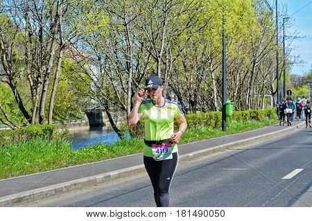 CLUJ-NAPOCA ROMANIA - APRIL 9 2017: CLUJ-NAPOCA ROMANIA - APRIL 9 2017: Unidentified young woman runs on the street dressed in sport outfit competing at the Wizz Air Cluj-Napoca Marathon.