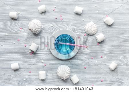 woman table trendy design with blue cocktail and marsh-mallow in soft light on wooden table background top view pattern