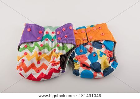 Two colorful washable baby panties with pattern and buttons lay on white background