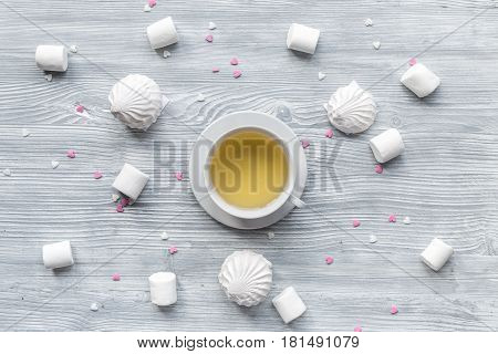 woman breakfast with cup of herbal tea and marsh-mallow on light wooden table background top view pattern