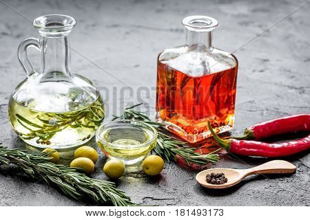 natural oils concept with fresh olives and chili paper and glass jars on stone table background