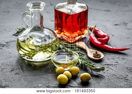 Glass bottles with bright chili and olive oils and herbs on stone table background