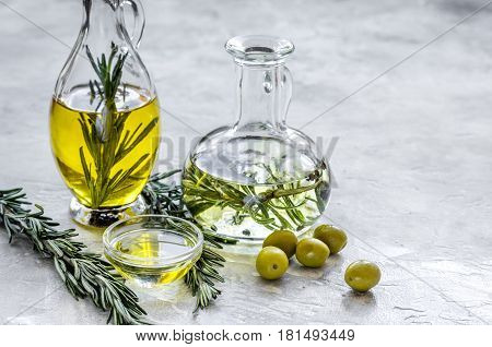 jar with natural oil with fresh olives and rosemary on stone table background mockup