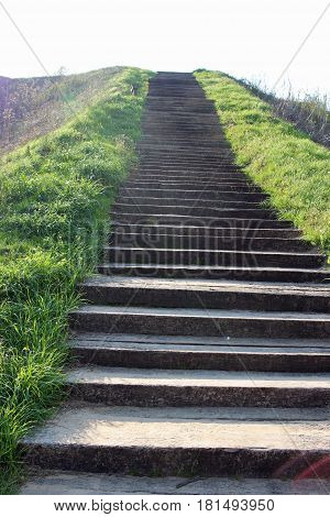 Concrete stairs leading up to sky with grass on either side